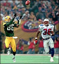 The Packers' Antonio Freeman catches an 81 yard touchdown pass as Lawyer Milloy looks on. (Globe Staff File Photo