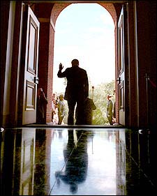 William F. Weld leaves the State House through the front doors after his resignation ceremony.