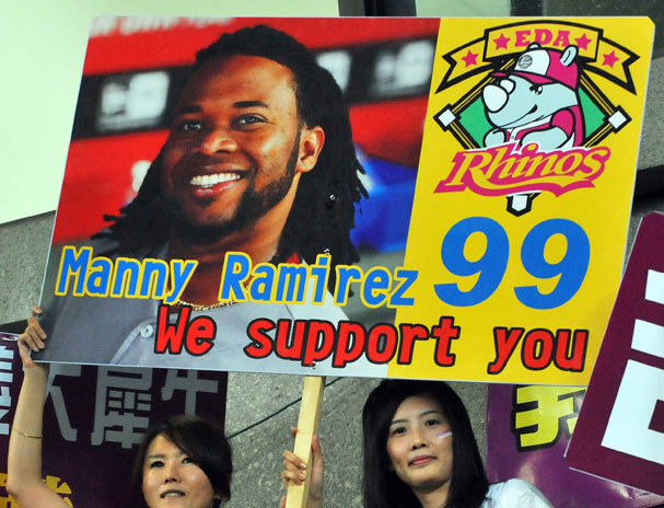 Two fans carry a placard in support of Manny Ramirez in his debut for game the EDA Rhinos baseball team in Kaohsiung, southern Taiwan ... only problem is, that's not our Manny on the sign.