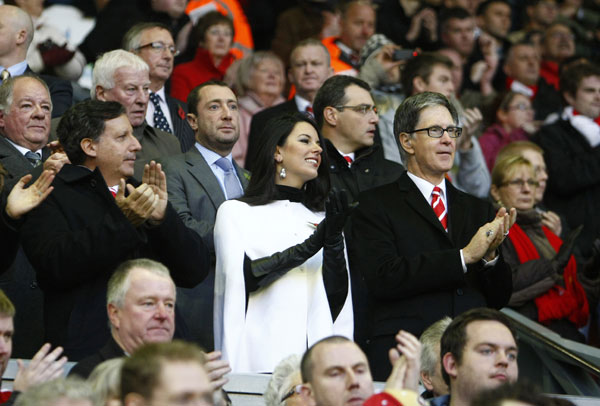 Liverpool co-owner John W Henry, right, stands alongside his partner Linda Pizzuti, center, and the club's Chairman Tom Werner, left, before the team's English Premier League soccer match against Chelsea at Anfield Stadium, Liverpool, England, Sunday Nov. 7, 2010.