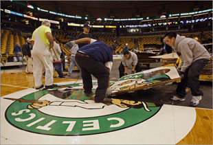 After the rink was deconstructed and the sub floor placed over the ice, members of the bull gang pieced together the famed Celtics playing surface -- the parquet. (Globe Staff Photo / Matthew J. Lee)
