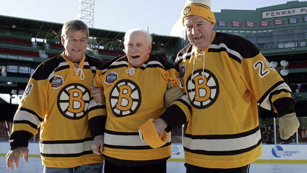 Former Boston Bruins greats Bobby Orr (left) and Terry O'Reilly (right) help Milt Schmidt off the ice while participating in the First Skate at Fenway Park event in Boston, Massachusetts December 18, 2009, in advance of the NHL Winter Classic game